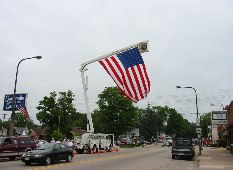 Large American flag hanging from high lifting truck pole in Clintonville