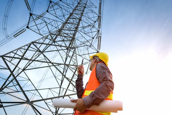 Construction worker checking high voltage tower